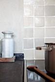 Zuckerstreuer aus Aluminium auf grauer Steinplatte neben Cerankochfeld mit Topf und Holzkochlöffel; handgearbeitete, helle Fliesen als Spritzschutz