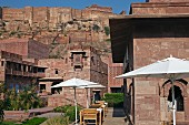 Outside view of Raas Haveli Hotel, Jodhpur, India with parasols, restaurant tables, gardens and view of mountain fortress