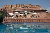 Restaurant tables and parasols next to swimming pool of Raas Haveli Hotel, Jodhpur, India