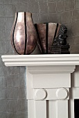 Different vases on mantelpiece against leather-covered wall