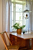 Country-style dining area - paraffin lamp hanging above wooden dining table at window