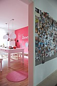 View from hallway with large collection of photos on wall into pink dining room with white dining table and pink rug