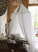 Bed with gauze canopy in room decorated in African style