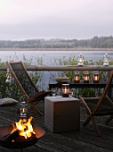 Deckchairs, fire bowl and lanterns on lakeside terrace