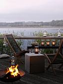 Terrasse mit Liegestühlen, Feuerkorb und Windlichtern am See