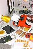 Orange typewriter and gold table lamp on desk