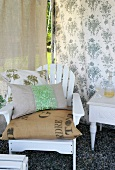 Various cushions on white-painted garden chair against floral interior wall of tent