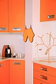 Fitted kitchen with orange fronts, orange oven gloves and matching tree-shaped rack for hanging utensils