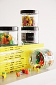 Screw-top jars of colourful boiled sweets on stack of comics
