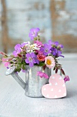 Garden posy in metal watering can with pink decorative heart