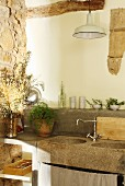 Concrete kitchen counter with stone sinks and vintage lamp against old masonry
