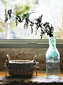 Leafy twig in glass bottle and linen-lined wicker basket on masonry window sill