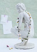 Key and daisy chain hanging on white china figurine