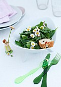 Green plastic cutlery and ornament of girl next to bowl of spinach salad with daisies