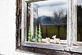 Altes Holzfenster mit kleinen Figuren an einem Bauernhaus