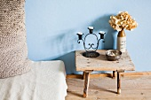 Candlestick and dried hydrangea on wooden footstool next to mattress