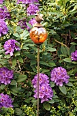 Ball stake with bird figure in front of purple-flowering rhododendron