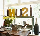 Vintage letters on metal shelves in front of large window