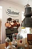 Altes Restaurant-Schild mit einer darunterhängenden Sammlung glänzender Kupferpfannen; im Vordergrund mehrere Glasglocken