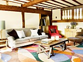 Rustic coffee table and antique sofa on patterned carpet in house with wooden half-timbered structure