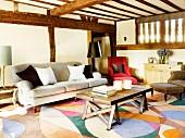 Rustikaler Couchtisch und antikes Polstersofa auf gemustertem Teppich in Wohnhaus mit Fachwerkkonstruktion aus Holz