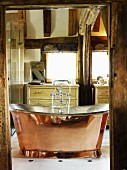 View through open door of vintage-style, free-standing copper bathtub in rustic setting