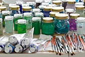 Artist's workbench: tubes of paint, paintbrushes and glass jars holding numerous paints