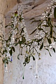 Christmas garland of glass beads, hand-blown glass droplets and mistletoe hanging in window niche in old, sandstone walls