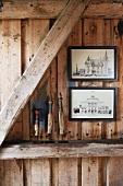 Bilder hängen an einer Holzwand, Holzbalken dienen als Ablage für Dekoobjekte