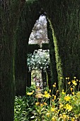Secretive garden path leading through topiary cypress trees