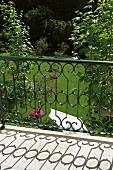 Metall Geländer mit gebogenen Stäben am Balkon und Blick in gepflegten Garten