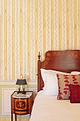 Detail of wooden bed headboard with marquetry veneer next to antique bedside table against striped wallpaper