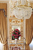 Chandelier in front of gilt console table with mirror flanked by gathered curtains