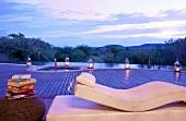 Luxuriöse Ruheliege vor Infinitypool unter weitem Abendhimmel
