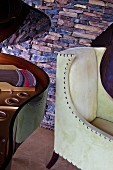 Stone wall behind open grand piano lid and elegant leather armchair