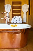 Exclusive copper bathtub with copper tap fittings; copper-coloured heated towel rail on wall in background