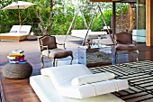 Wooden terrace with modern, upholstered furnishings, large couch and Baroque armchairs flanking chrome trunk used as side table
