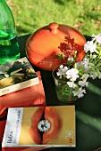 Bücher, Blume und Topf auf einem Gartentisch