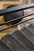 View from black metal stairs down onto multicoloured parquet floor and round sculpture