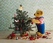 Festive teddy bear decorating little Christmas tree with various baubles lying on floor