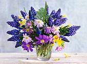 Frühlingsblumenstrauss mit Traubenhyazinthen, Anemonen und Primeln