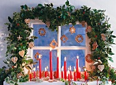 A window decorated with a garland, burning candles and Christmas biscuits