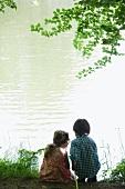 Girl and boy fishing on lake shore