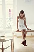 Mädchen in Kleid und Stiefeln sitzt auf einem Tisch im Zimmer