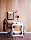 Office chair and white table on castors below pendant lamp with copper lampshade against wooden wall