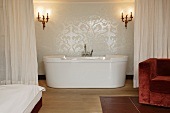 En suite bathroom separated by curtain with modern free-standing bathtub below antique sconces (Schloss Schauenstein)