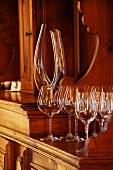 Simple, modern wine glasses and elegant carafe on antique dresser (Schloss Schauenstein)