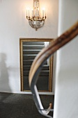 Stone staircase reflected in gilt-framed mirror with blurred handrail in foreground