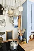 Modern trifft Alt in einfacher Küche mit Ceranherd und antiken Küchenutensilien