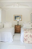 Bright, airy bedroom with antique bedside cabinet between twin beds
